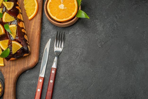 Mezzo colpo di torte morbide a bordo e limoni tagliati con foglie sul tavolo scuro