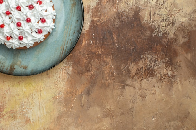 Half shot of tasty cake decorated with cream and currant on a blue plate on the right side on a colorful background