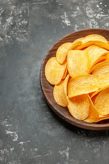 Half shot of tasty homemade potato chips on a brown plate on gray table