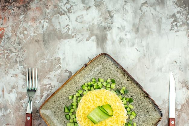 Mezzo colpo di gustosa insalata servita con cetriolo tritato e forchetta a coltello su sfondo a colori misti