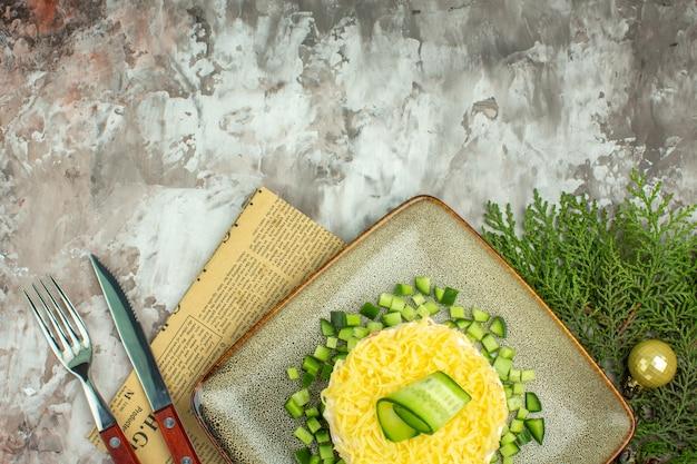 Mezzo colpo di gustosa insalata servita con cetriolo tritato e forchetta coltello su un vecchio giornale