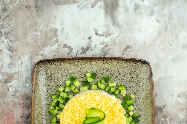 Half shot of tasty salad served with chopped cucumber on mixed color background