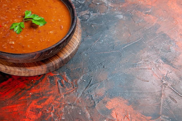 Half shot of tomato soup on a brown cutting board on a mixed color table
