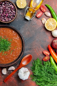 Mezzo colpo di zuppa di pomodoro olio bottiglia fagioli limone e un mazzo di verde sulla tabella di colori misti