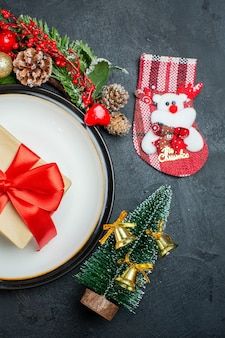 ディナープレートのギフトボックスのハーフショットビュークリスマスツリーモミの枝針葉樹の円錐形サンタクロース帽子落ちたガラスのゴブレット暗い背景に
