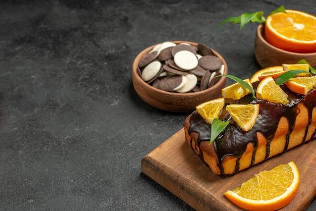 맛있는 케이크의 절반 샷보기는 어두운 테이블에 커팅 보드에 비스킷과 오렌지를 잘라