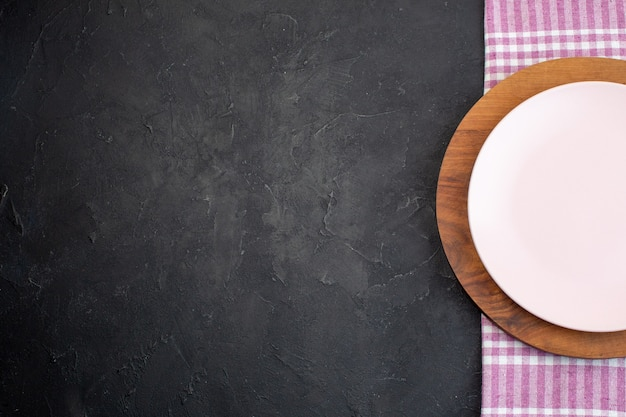 Half shot of white and brown ceramic empty plates on black background with free space
