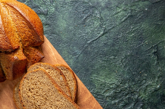 Half shot of whole and cut black bread on brown wooden cutting board on dark colors background