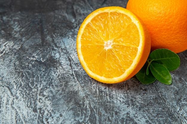 Mezzo colpo di arance fresche intere e tagliate a metà su sfondo grigio