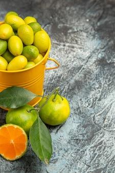 Mezza ripresa di un secchio giallo pieno di mandarini verdi freschi e tagliato a metà mandarini su sfondo grigio