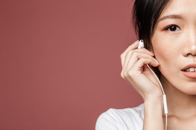 붉은 벽 위에 이어폰을 꽂고 음악을 들으며 기본 옷을 입은 갈색 머리 아시아 여성의 반쪽 초상화