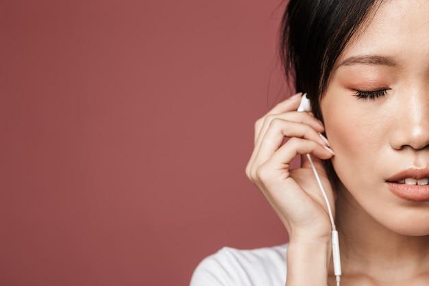 빨간 벽에 격리된 이어폰으로 음악을 들으며 기본 옷을 입은 귀여운 아시아 여성의 반쪽 초상화
