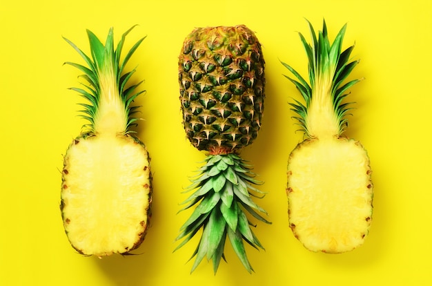 Half slice of fresh pineapple and whole fruit on yellow