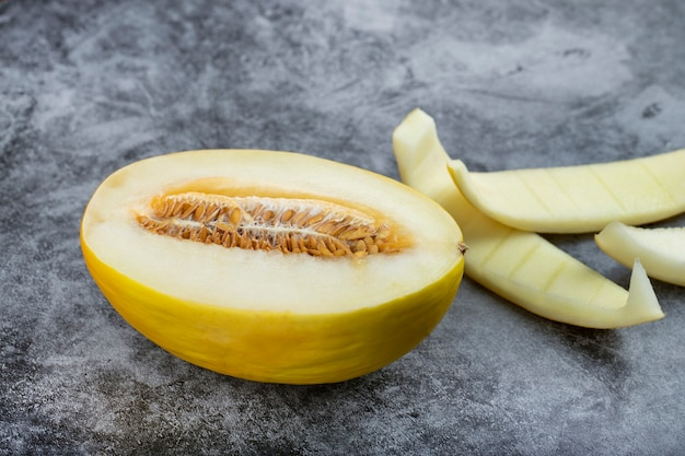 Half sliced honeydew melon with its skin on marble background.