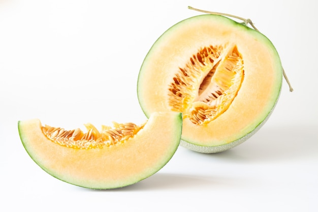 Half and sliced japanese melons isolated on white background