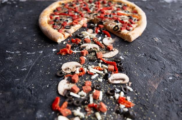 Mezza pizza a fette e ingredienti su una tavola di pietra nera