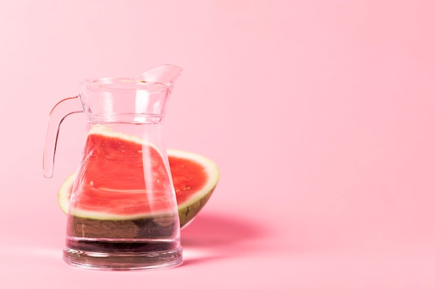 Half sliced watermelon with jug of water