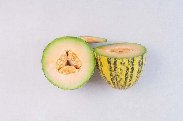 Mezze fette di melone verde sul tavolo bianco.