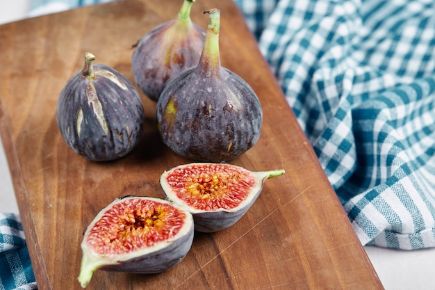 Half slices and whole figs on wooden board with a blue tablecloth.