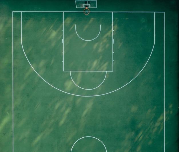Half sports basketball playground with green grass