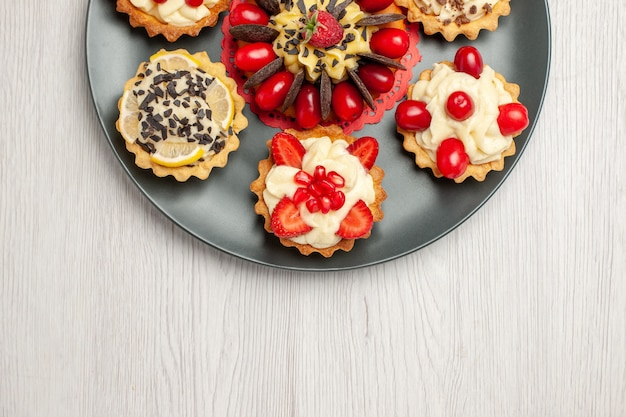 Half-top close view chocolate cake rounded with berry tarts in the grey plate at the top center of the white wooden table with copy space