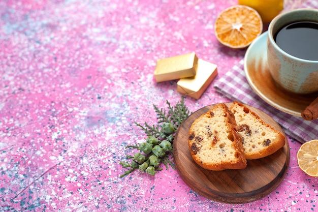 Torta squisita vista ravvicinata semi-superiore affettata con tazza di tè, cannella e limoni sulla scrivania rosa chiaro.
