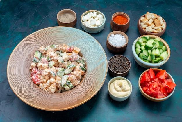 プレート内のハーフトップマヨネーズ野菜サラダ、スライスした野菜と暗い机の上の調味料、フードミール野菜サラダ