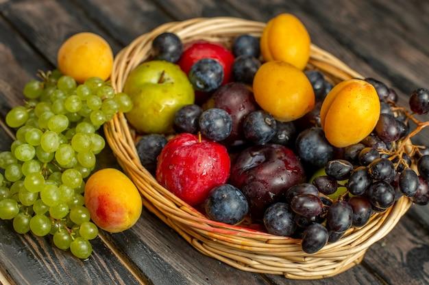 Корзина с видом на половину сверху с сочными и кислыми фруктами, такими как виноград, абрикосы, сливы, на коричневом столе