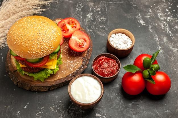 Hamburger di carne di formaggio con vista a mezza altezza con condimenti su panino con patatine fritte di superficie scura