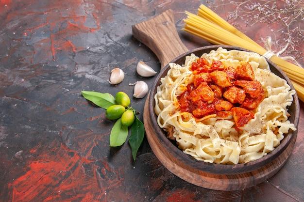 Pollo con vista dall'alto a metà con un piatto di pasta sulla superficie scura pasta scura del piatto