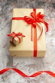 白い写真のホリデーカラー新年ギフトクリスマスに赤いリボンが付いたハーフトップビューのクリスマスプレゼント