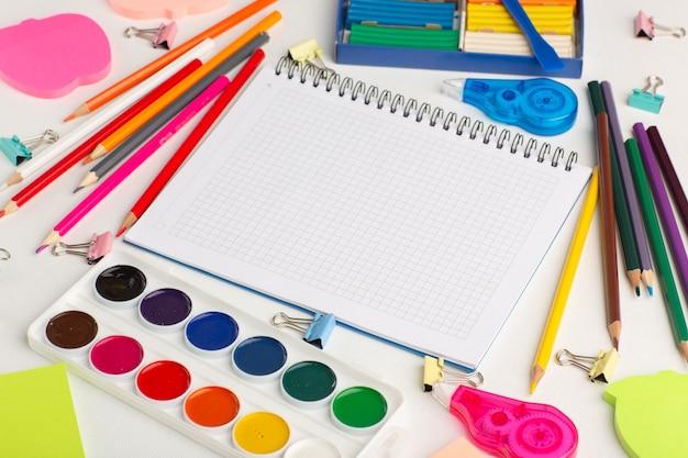 Matite colorate con vista a metà superiore con vernici e adesivi su vernice a colori per disegno arte scrivania bianca