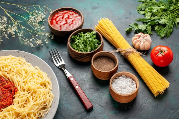 青い表面に肉とさまざまな調味料を使ったハーフトップビューの調理済みイタリアンパスタ