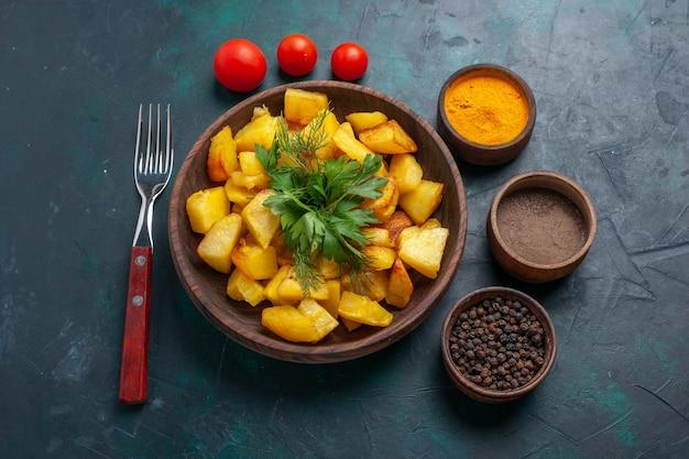 Вареный картофель с приправами на темно-синей поверхности, вид сверху