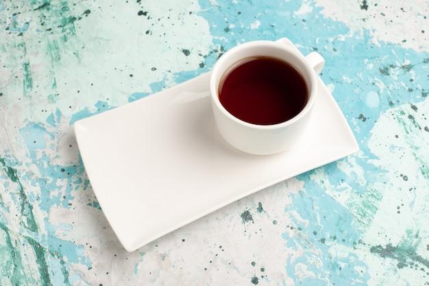 水色の机の上のカップとプレートの中にお茶のハーフトップビューカップ