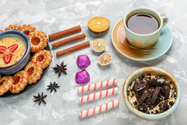 ライトホワイトのデスククッキーチョコレートケーキ焼きパイシュガースウィートにチョコレートクッキーデザートとジャムクッキーを添えたハーフトップビューのお茶