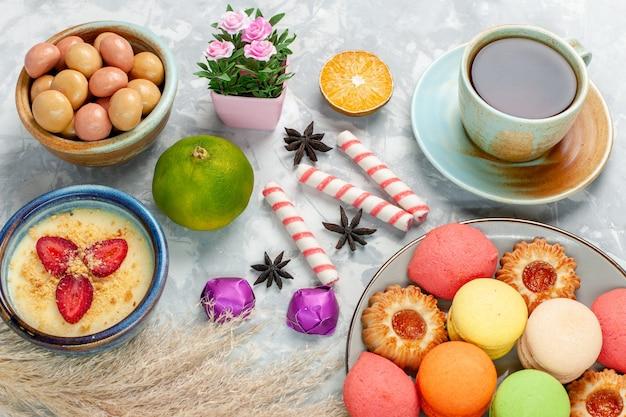Чашка чая с десертным печеньем, пирожными и конфитюрами на светло-белой поверхности, конфеты, сладкий фруктовый чай