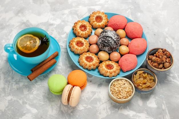 흰색 표면에 프랑스어 마카롱 쿠키와 케이크와 차의 절반 상단보기 컵
