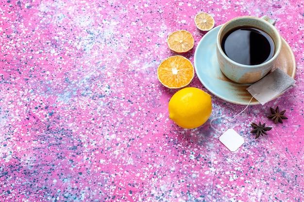 ピンクの机の上にレモンとお茶のハーフトップビューカップ。