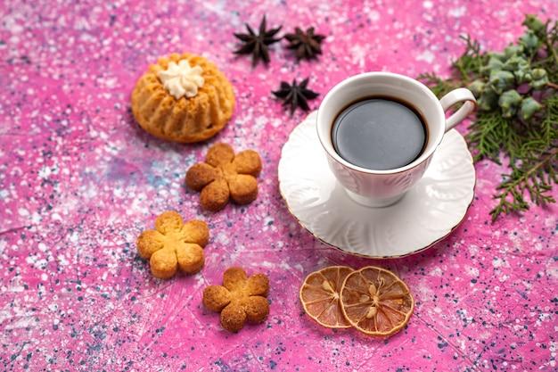 Чашка чая с небольшим тортом и печеньем на светло-розовом столе, вид сверху.