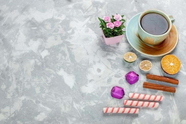 Tazza di tè con cannella e caramelle sulla scrivania leggera con vista dall'alto