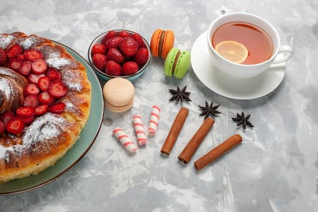 Tazza di tè con vista dall'alto a metà con macarons francesi e torta su una superficie bianco chiaro