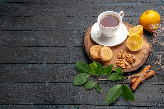 Tazza di tè mezza vista con frutta e biscotti