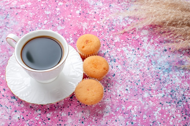 Half-top view of cup of tea with little cakes on the pink surface
