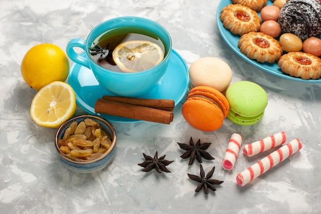 Tazza di tè con vista dall'alto a metà con macarons e uvetta sulla superficie bianca