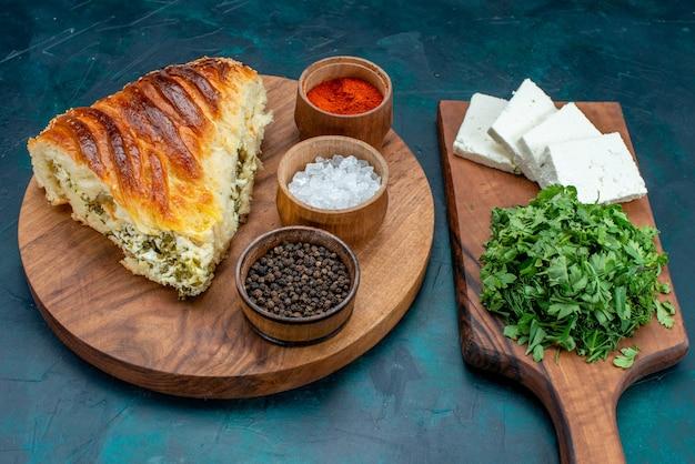 Вкусная выпечка, вид сверху, нарезанная зеленью, начинкой с приправами и сыром на темном фоне.
