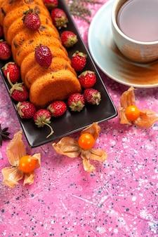 ピンクの机の上に新鮮な赤いイチゴとお茶を入れた黒いケーキパンの中のハーフトップビューのおいしいケーキ。