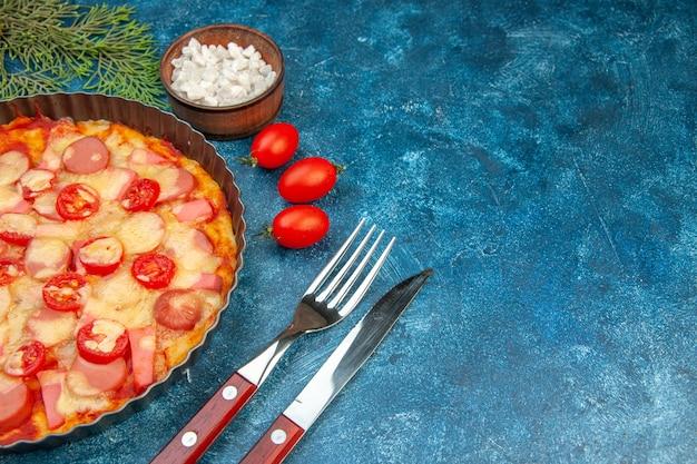 Vista dall'alto deliziosa pizza al formaggio con salsicce e pomodori su sfondo blu torta di pasta alimentare foto a colori fast-food italiano