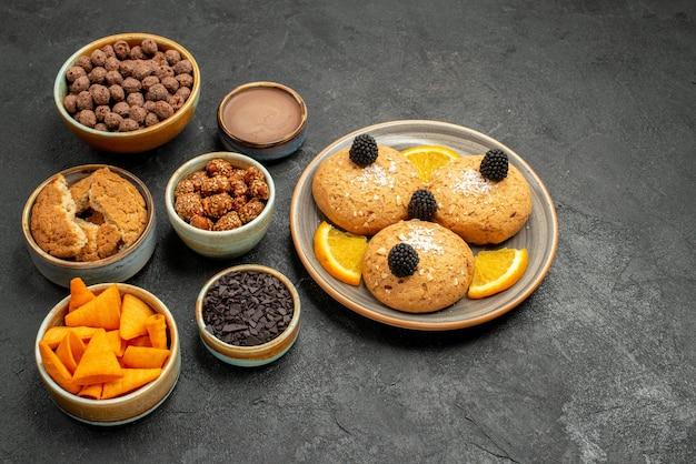ダークグレーの背景にチップとナッツが入ったハーフトップビューのおいしいクッキークッキービスケットティースイートケーキ