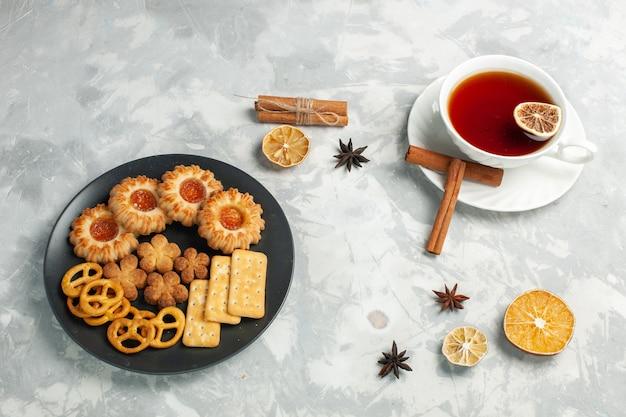 밝은 흰색 책상에 차 한잔과 함께 접시 안에 크래커와 칩이 들어간 하프 탑 뷰 맛있는 쿠키